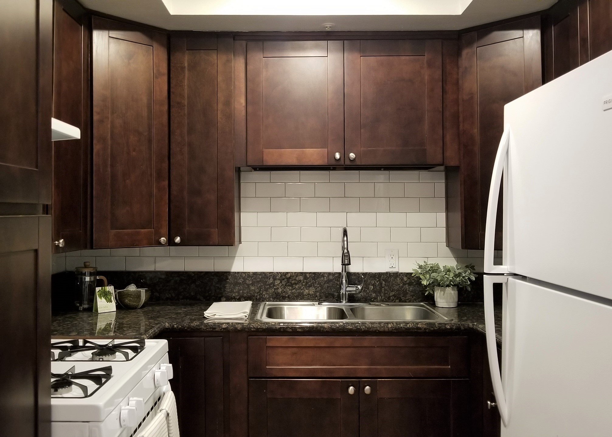 Kitchen cabinetry, stove, granite counter top, and refrigerator